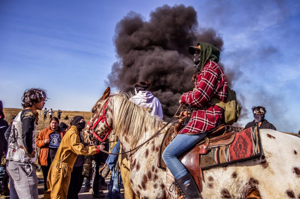 Water Protectors Behind a Burning Barricade Rob Wilson Photography